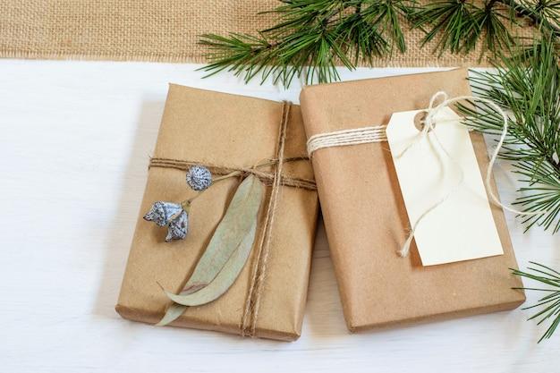 Ręcznie robione alternatywne pudełka na prezenty świąteczne zawinięte w papier rzemieślniczy grunge, gałęzie choinek na białym tle