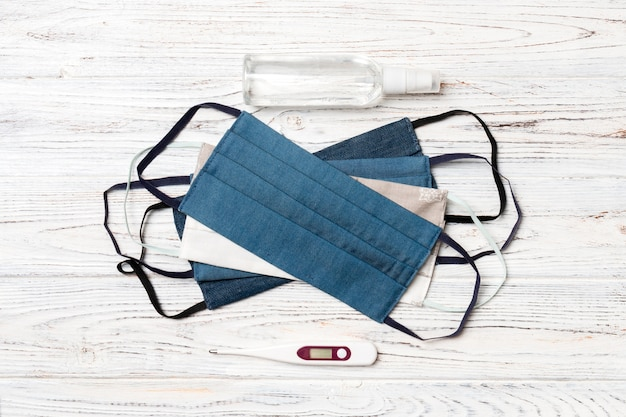 Ręcznie robione bawełniane maski, cyfrowy termometr i odkażacz alkoholowy