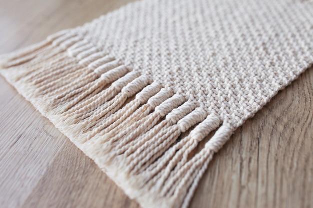 Ręcznie robione beżowe tło makramy. struktura makramy, przyjazna dla środowiska, nowoczesna dzianina. dywan z makramy na drewnianym stole