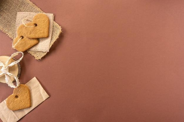 Ręcznie robione ciasteczka w kształcie serduszka leżą na krefowanej papierowej torbie.