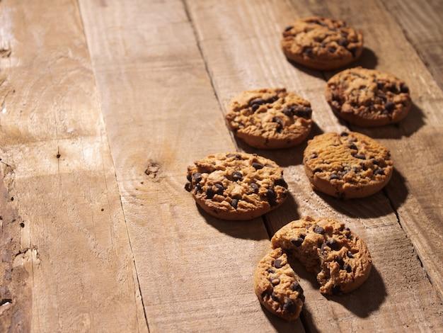 Ręcznie robione ciasteczka z kawałkami czekolady na rustykalnym ciemnym tle drewna