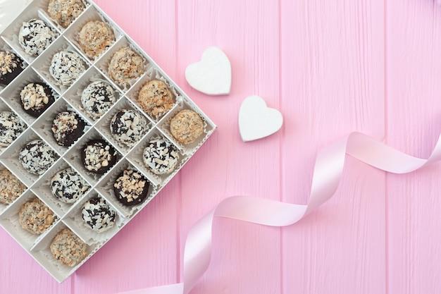 Ręcznie robione cukierki czekoladowe na różowym drewnianym stole. pudełko czekolady otwarte z dwoma sercami i świąteczną wstążką.