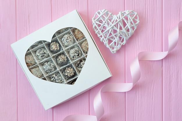 Ręcznie robione cukierki czekoladowe na różowym drewnianym stole