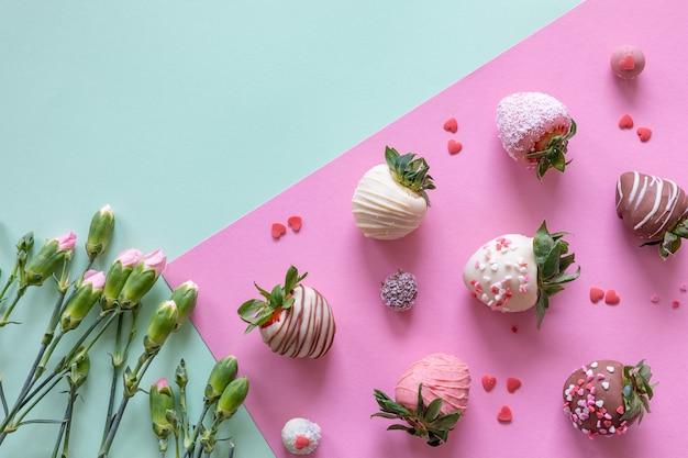 Ręcznie robione czekoladki pokryte truskawkami i kwiatami na kolorowym tle z bezpłatną przestrzenią na tekst