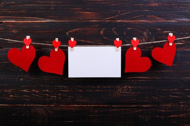 Ręcznie robione czerwone filcowe serca i biały papier wiszący na sznurze z spinaczami do bielizny
