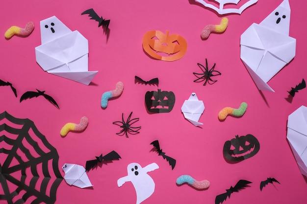 Ręcznie robione dekoracje na halloween i gummy robaki na różowym tle. halloweenowy tło. widok z góry. płaskie ułożenie