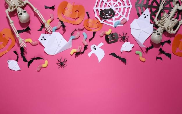 Ręcznie robione dekoracje na halloween i szkielet, gummy robaki na różowym tle. halloweenowy tło. skopiuj miejsce. widok z góry. płaskie ułożenie