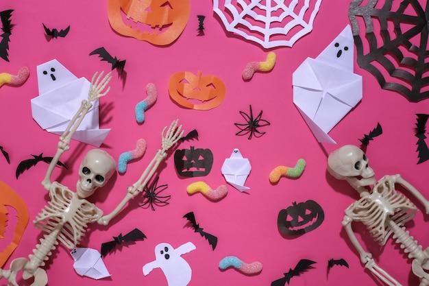 Ręcznie robione dekoracje na halloween i szkielet, gummy robaki na różowym tle. halloweenowy tło. widok z góry. płaskie ułożenie