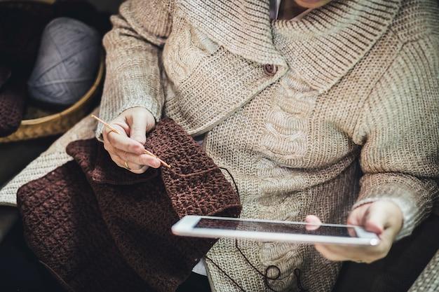Ręcznie robione hobby pozostanie w domu koncepcja, szczęśliwa azjatycka stara kobieta robi na drutach brązowy szalik na szydełku i tablet na kanapie w salonie w domu