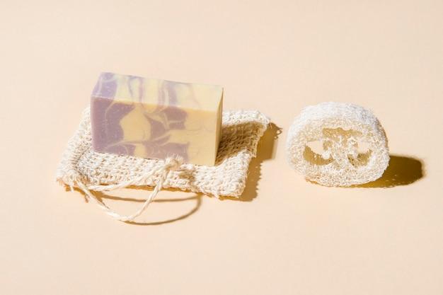 Ręcznie robione mydło konopne i gąbki z luffy na beżowym tle. koncepcja stylu życia ekologicznego.