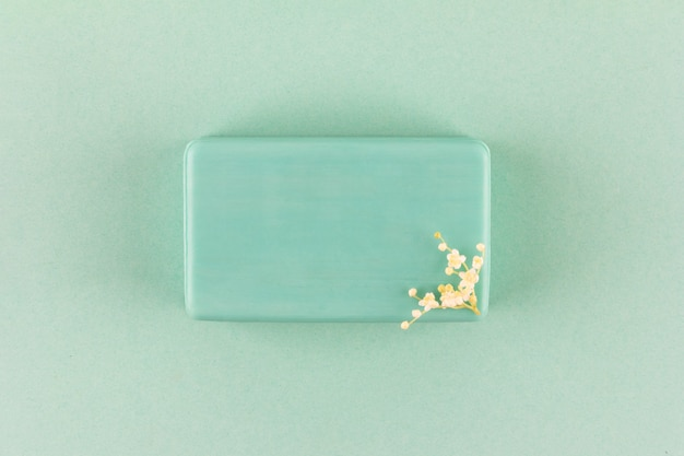 Ręcznie robione mydło w kostce z małymi białymi kwiatami na zielonym tle widok z góry