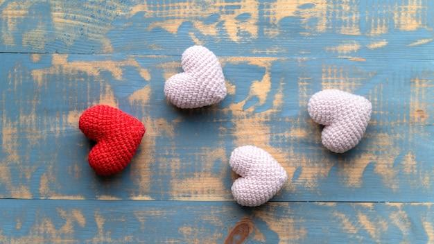 Ręcznie robione na drutach jedno czerwone i trzy różowe serduszka. widok z góry