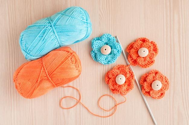 Ręcznie robione na drutach szydełkowe kwiaty i drewniane koraliki. widok z góry
