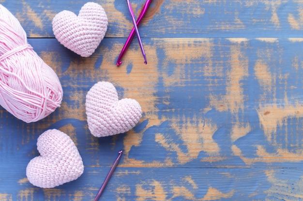 Ręcznie robione na drutach trzy różowe serduszka z kłębkiem włóczki. widok z góry