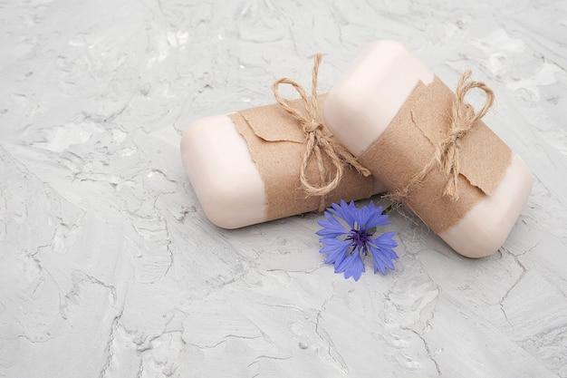 Ręcznie robione naturalne mydło ozdobione papierem rzemieślniczym, biczem i niebieskimi kwiatami.