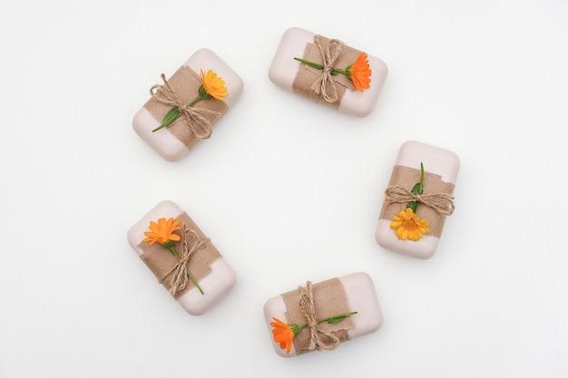 Ręcznie robione naturalne mydło ozdobione papierem rzemieślniczym i pomarańczowym kwiatem nagietka