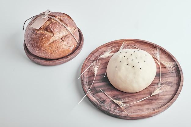 Ręcznie robione okrągłe ciasto chlebowe z ugotowanym na drewnianym talerzu.