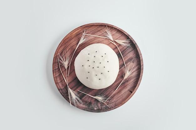 Ręcznie robione okrągłe ciasto na bułkę na drewnianym talerzu.
