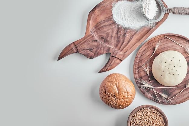 Ręcznie robione okrągłe ciasto na chleb na drewnianym talerzu z ugotowanym na bok.