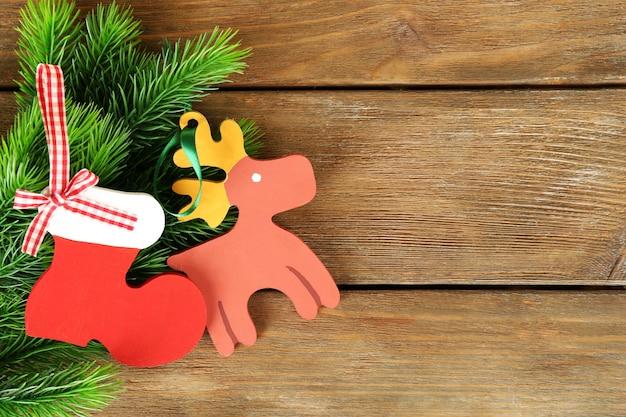 Ręcznie robione ozdoby świąteczne i gałąź jodły na drewnianym tle