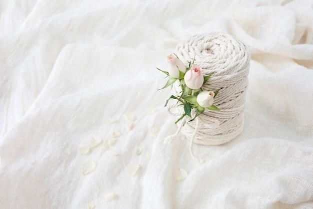 Ręcznie robione plecionki z makramy i bawełniane nici z kwiatem róży na białej pościeli