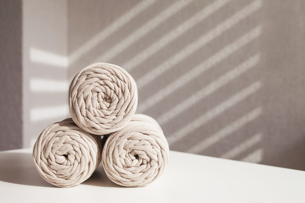 Ręcznie robione plecionki z makramy i naturalne bawełniane nici układają się na białym tle z cieniami