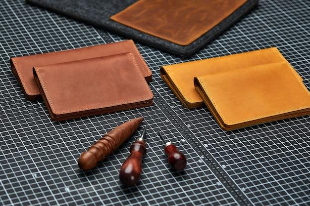 Ręcznie robione produkty z prawdziwej skóry w kolorze żółtym i czerwonym. skórzana okładka paszportu, skórzany portfel. galanteria skórzana dla mężczyzn. widok z góry.