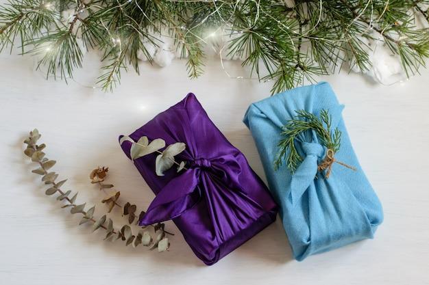 Ręcznie robione pudełka na prezenty świąteczne, owinięte tkaniną w tradycyjnym japońskim stylu furoshiki.