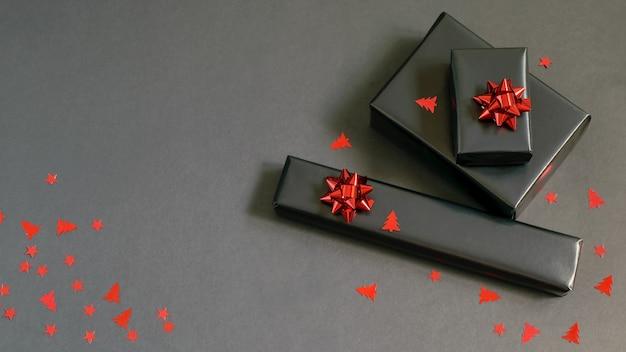 Ręcznie robione pudełka na prezenty świąteczne zapakowane w czarny papier, błyszczące czerwone wstążki i świąteczne konfetti. ręcznie robione prezenty, pomysły na majsterkowanie.