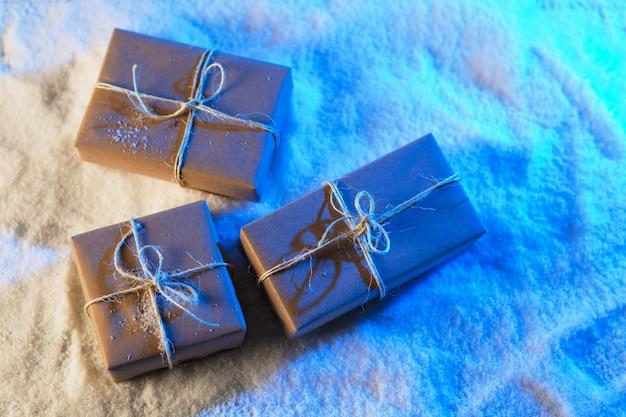 Ręcznie robione pudełka na prezenty z papieru rzemieślniczego na zaśnieżonym drewnianym stole w niebieskim świetle.
