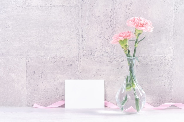 Ręcznie robione pudełko upominkowe z niespodzianką na dzień matki życzy fotografii - piękne kwitnące goździki z pudełkiem z różową wstążką na białym tle na szarym projekcie tapety, zbliżenie, kopia przestrzeń, makieta