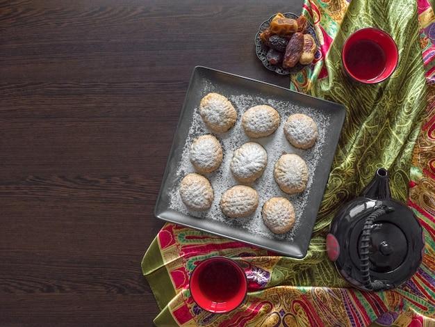 """Ręcznie robione słodycze ramadan podawane są z herbatą na ciemnym drewnianym stole. egipskie ciasteczka """"kahk el eid"""" - ciasteczka z islamskiej uczty el fitr. widok z góry"""