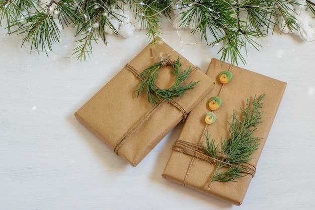 Ręcznie robione, zapakowane w papier rzemieślniczy prezenty na świątecznym stole wigilijnym