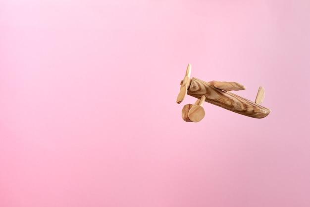 Ręcznie robiony drewniany samolot zabawka latający na pastelowym różowym tle. ścieśniać.