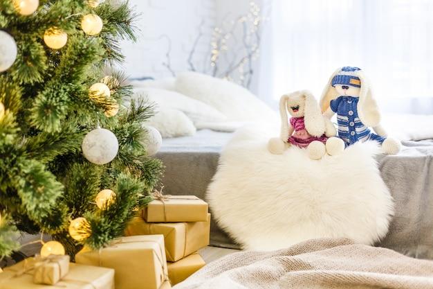 Ręcznie robiony dzianinowy królik. króliczek w szaliku i czapce z dużym pomponem wśród ozdobnych choinek i bombek. kompozycja świąteczna