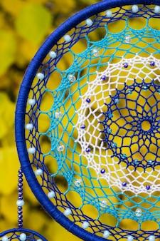 Ręcznie robiony łapacz snów z zawieszonymi nitkami z piór i koralikami