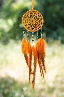 Ręcznie robiony łapacz snów z zawieszonymi piórkami i koralikami