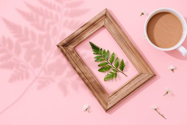 Ręcznie robiony minimalistyczny botaniczny wystrój wnętrz, zielone tropikalne liście w drewnianych ramach wiszących na różowym tle