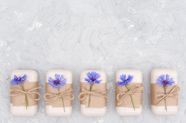 Ręcznie robiony naturalny zestaw mydła ozdobiony papierem rzemieślniczym, biczem i niebieskimi kwiatami. koncepcja kosmetyków organicznych.