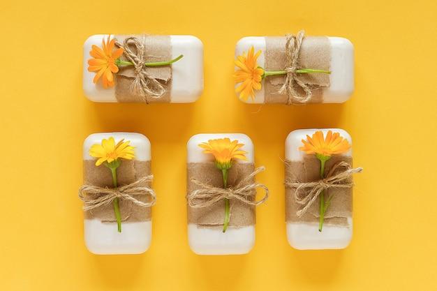 Ręcznie robiony naturalny zestaw mydła ozdobiony papierem rzemieślniczym, biczem i pomarańczowymi kwiatami nagietka