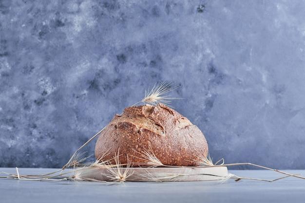 Ręcznie robiony okrągły chleb na drewnianej desce.