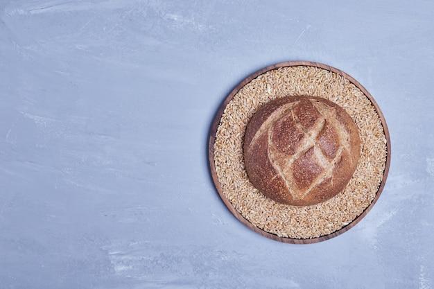Ręcznie robiony okrągły chleb na drewnianym talerzu, widok z góry.