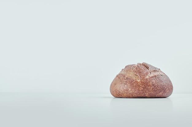 Ręcznie robiony okrągły chleb na szarym stole.