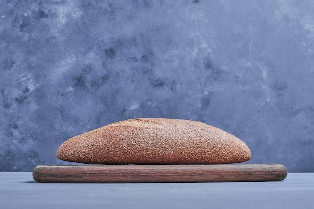Ręcznie robiony owalny chleb na szarym stole na drewnianej desce.