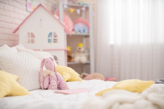 Ręcznie robiony pluszowy królik wykonany z tkaniny siedzi na wygodnym łóżku w pokoju dziecięcym.