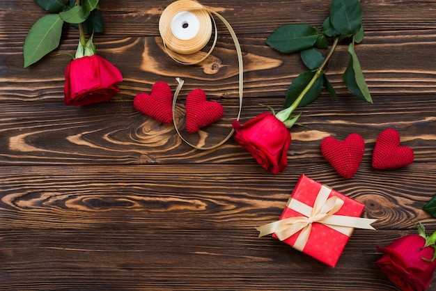 Ręcznie robiony prezent walentynkowy lub inny świąteczny z czerwonym sercem i pudełkiem na prezenty w świątecznym opakowaniu. teraźniejsza pudełkowata dekoracja prezent na drewnianym stołowym odgórnym widoku z kopii przestrzenią, pusta przestrzeń dla projekta.