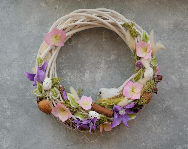 Ręcznie robiony wieniec wielkanocny z kwiatami i ptaszkiem na szarym stole. koncepcja wakacje i wiosna.