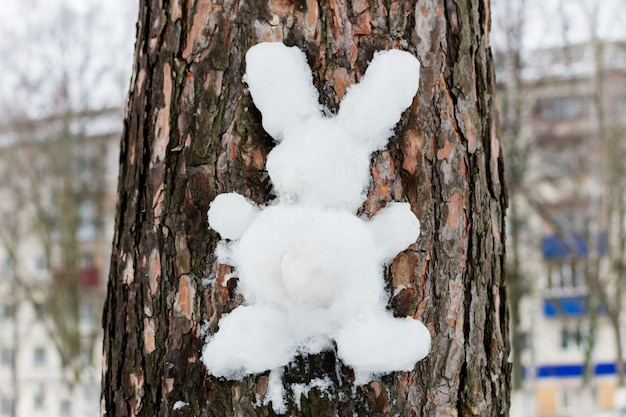 Ręcznie robiony zając lub królik wykonany z białego śniegu na korze drzewa. zimowe zabawy na świeżym powietrzu, zabawa bożonarodzeniowa, symbol wielkanocy. wysokiej jakości zdjęcie