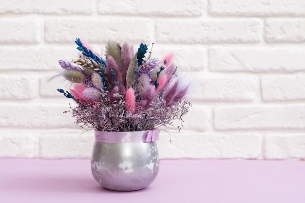 Ręcznie robiony zestaw suszonych kwiatów. bukiet z naturalnej gałęzi, pszenicy, roślin, dzikiej trawy. kompozycja florystyczna na tle z białego ceglanego wystroju.