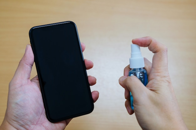 Ręcznie rozpylając żel alkoholowy na smartfona